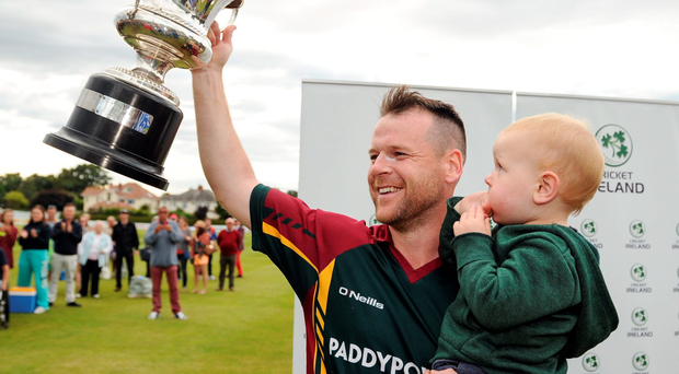 Merrion captain Dom Joyce lifts the cup with son Alexander following his team's victory during the Irish Cricket Senior Cup Final against Waringstown at Castle Avenue in Clontarf. Photo: Sportsfile