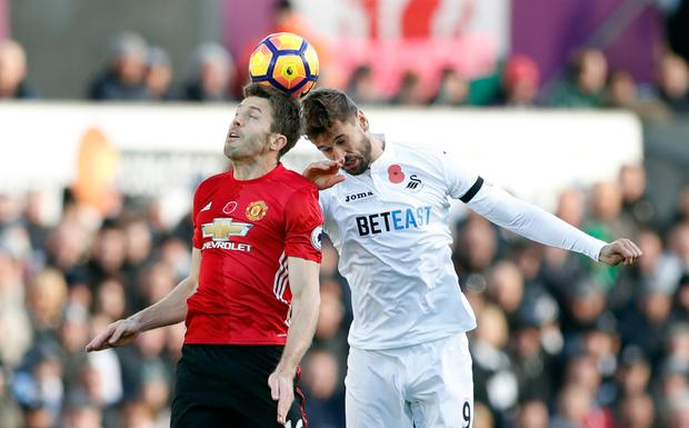 Man United's Michael Carrick in action with Swansea's Fernando Llorente