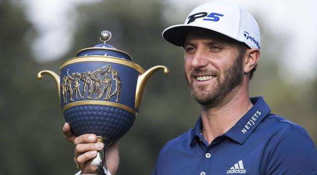Dustin Johnson poses with the trophy (AP)