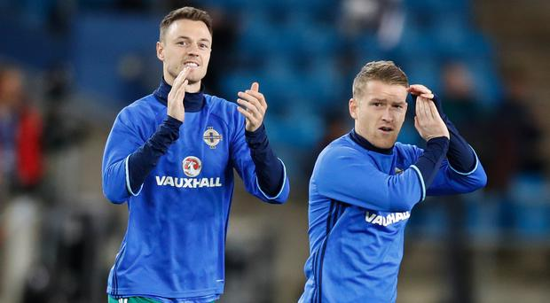 Jonny Evans, left, and Steven Davis came out for their warm-up minutes after Northern Ireland's play-off place was confirmed