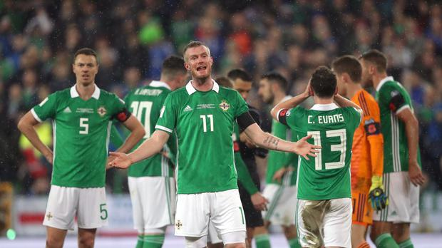Northern Ireland's players react with disbelief after a penalty for handball is awarded against Corry Evans