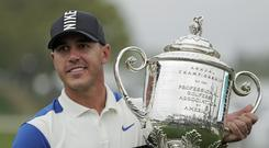 Brooks Koepka holds up the Wanamaker Trophy after winning the US PGA Championship (AP Photo/Julio Cortez)