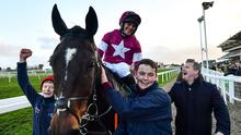 Rob James pictured after winning the Fulke Walwyn Kim Muir Challenge Cup Amateur Riders' Handicap Chase on Milan Native, left, with trainer Gordon Elliott, right, on Day Three of the Cheltenham Festival last year