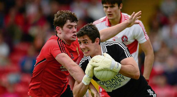 Derry goalkeeper Eoin McNicholl keeps hold of the ball as he comes under pressure from Niall Madine