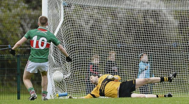 Dr Crokes goalkeeper David Moloney can't stop Loughmore-Castleiney's John McGrath scoring from a penalty during the Munster club semi-final