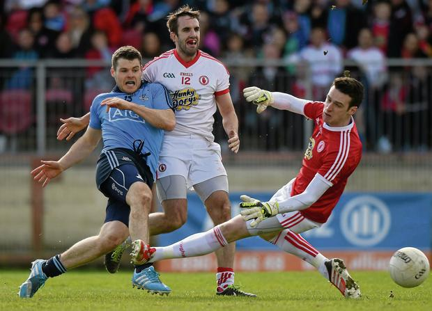 Dublin's Kevin McManamon shrugs off Mark Donnelly and fires past Tyrone goalkeeper Niall Morgan only to have his shot cleared off the line in Omagh