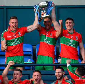Ballymun Kickhams captain James McCarthy, centre, lifts the Clerys Perpetual Cup alongside Paddy Small, left, and John Small after their Dublin SFC final win against Ballyboden St Enda's. Photo: Sportsfile