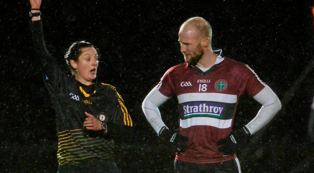 Maggie Farrelly issues a yellow card to Danny McBride of St Mary's during Wednesday's rain-lashed McKenna Cup game in Garvaghey (Photo: Sportsfile)