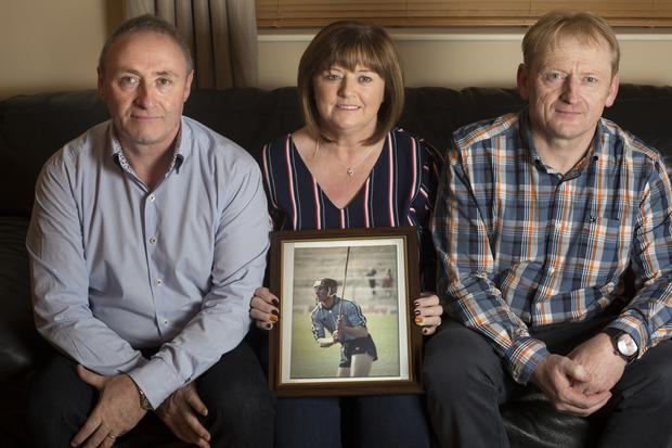 Brendan Mulhere, Fidelma Byrne and James Mulhere hold a photo of their brother, Paul. Photo: Tony Gavin