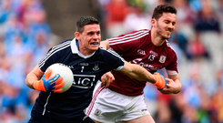 At arm's length: Stephen Cluxton holds off Ian Burke during Dublin's All-Ireland semi-final victory over Galway in which, as so often this year, the opponents never really got close to Jim Gavin's men