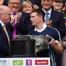 GAA director-general Tom Ryan (left) looks on while president John Horan presents the Sam Maguire Cup to Dublin captain Stephen Cluxton. Photo: Brendan Moran