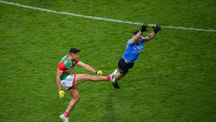 Tommy Conroy gets a shot away despite an attempted block by David Byrne. Photo: Stephen McCarthy/Sportsfile