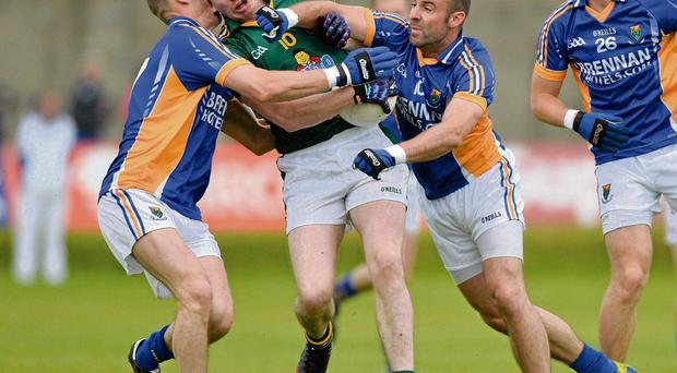 Meath's Peadar Byrne comes under pressure from Dean Healy and Darragh O'Sullivan.
