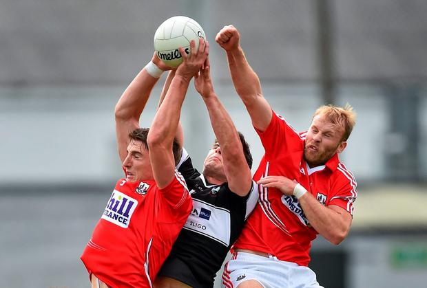 Aidan Walsh, Cork, left, supported by teammate Michael Shields, contests a high ball with Pat Hughes, Sligo