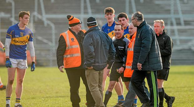 Referee David Coldrick is escorted off the field by stewards as Tipperary manager Peter Creendon has words with him