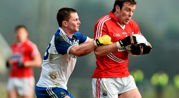James Loughrey, Cork, is tackled by Dermot Malone, Monaghan