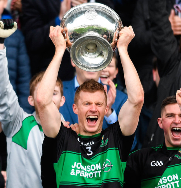 Alan Cronin lifting the cup for Nemo. Photo: Sportsfile
