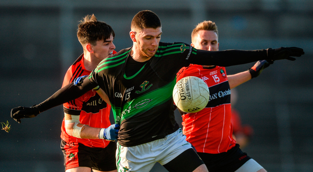 Luke Connolly of Nemo Rangers has his jersey pulled as he comes under pressure from Eoin Ryan and Mark Connolly of Adare during yesterday's clash in Mallow Photo: Sportsfile