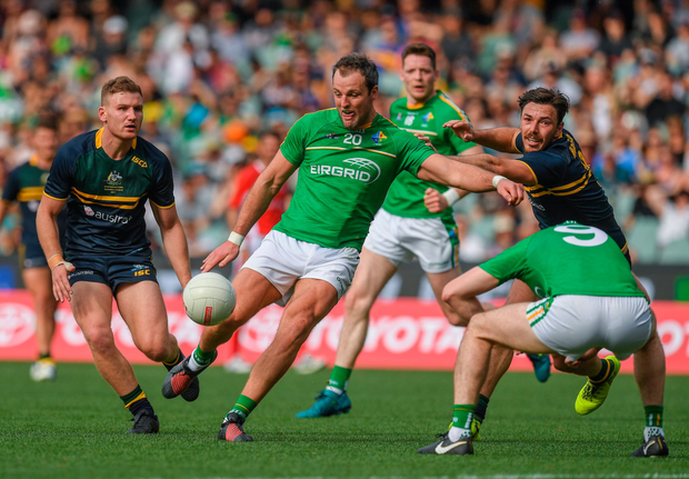 Paul Geaney ducks as Ireland team-mate Michael Murphy fires in a shot under pressure from Michael Hibberd of Australia Photo: Sportsfile