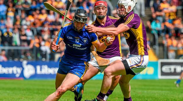 John Conlon, Clare, in action against Ciarán Kenny, right, and Eoin Moore, Wexford