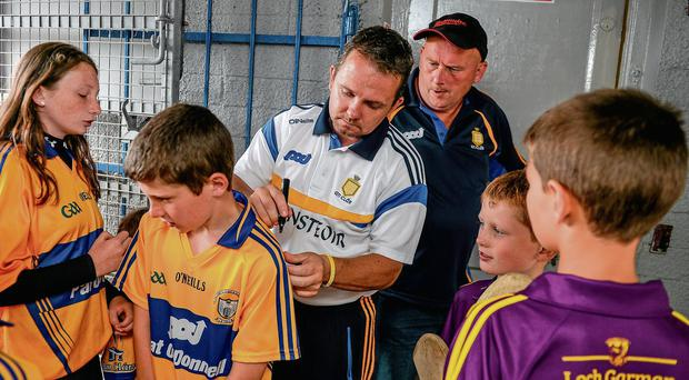 Davy Fitzgerald signs the jerseys of young Clare fans