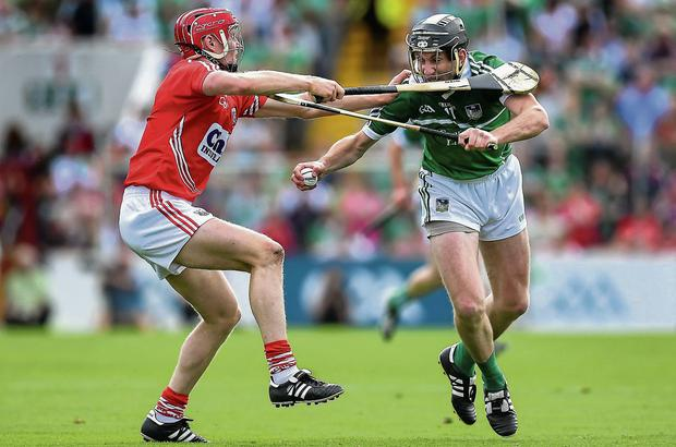 Limerick's Donal O'Grady attempts to get past the challenge of Cork's Lorcan McLoughlin
