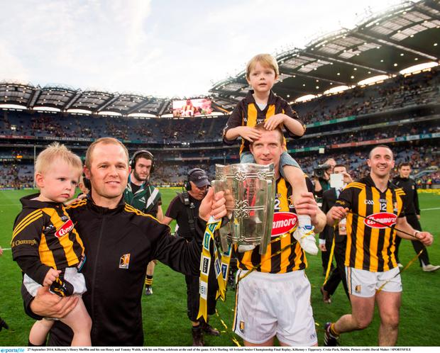 Kilkenny's Henry Shefflin and his son Henry and Tommy Walsh, with his son Finn, with the Liam McCarthy cup. Photo: David Maher / SPORTSFILE.
