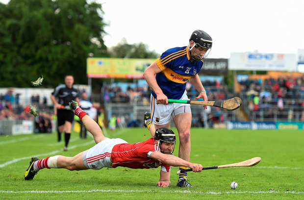 Tipperary's John McGrath tries to escape the clutches of Cork defender Mark Ellis in Thurles yesterday. Photo: Sportsfile