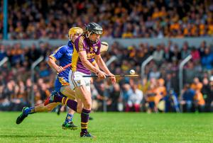 Liam Óg McGovern, Wexford, is tackled by Colm Galvin, Clare