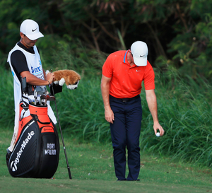 Rory McIlroy takes a drop from knee-height at Kapalua Golf Club on Friday. Photo: Getty