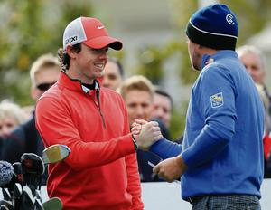 Rory McIlroy and Graeme McDowell greet each other on the first tee at Wentworth yesterday