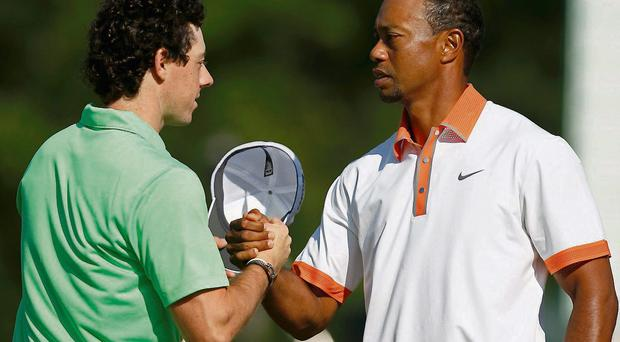 Rory McIlroy and Tiger Woods shake hands at practice in Merion yesterday