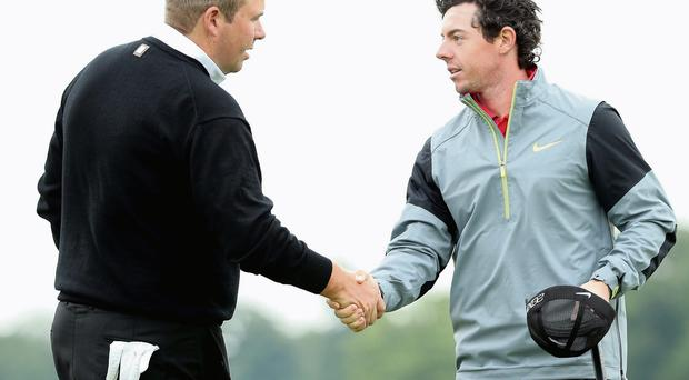Shane Lowry of Ireland shakes hands with Rory McIlroy at the end of their first round of the Irish Open at Carton House