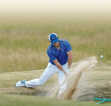 Rory McIlroy splashes out a bunker onto the 18th green during a practice round ahead of The Open at Muirfield