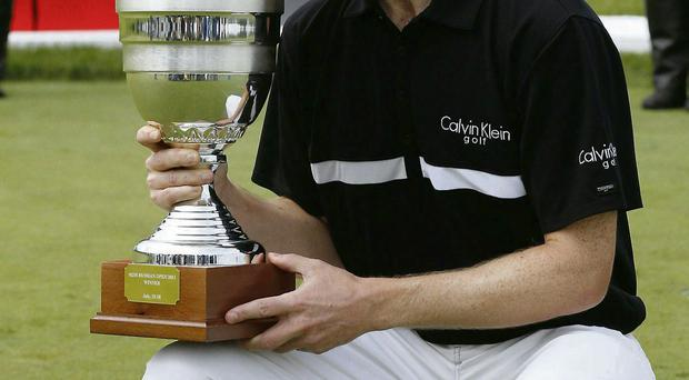Northern Ireland's Michael Hoey kisses his trophy while two carabineers salute for his win in the final round at the Russian Open golf tournament at Tseleevo Golf and Polo Club in Moscow