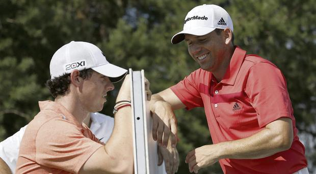 Rory McIlroy chats with Sergio Garcia between the 11th tee and 18th tee during the pro-am of the BMW Championship in Chicago