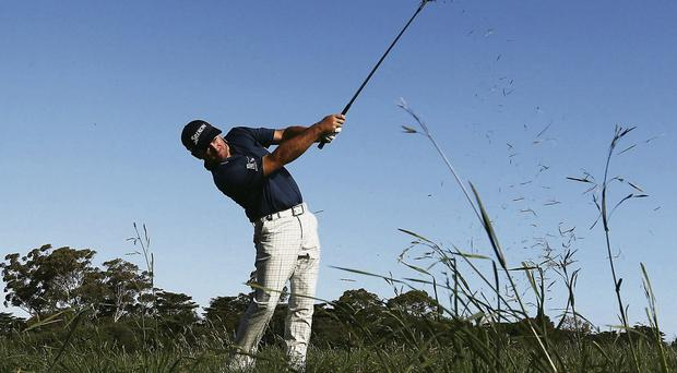 Graeme McDowell plays out of the rough during the first round of the World Cup of Golf at Royal Melbourne