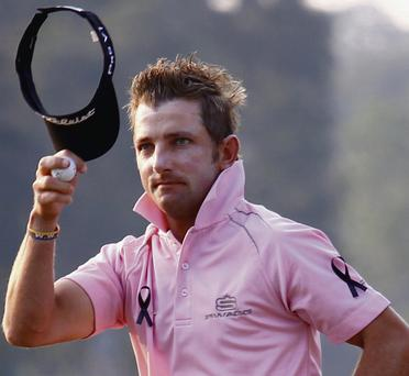 Jbe Kruger of South Africa, wearing black ribbons in memory of the late Nelson Mandela, acknowledges spectators after finishing his second round at the Hong Kong Open