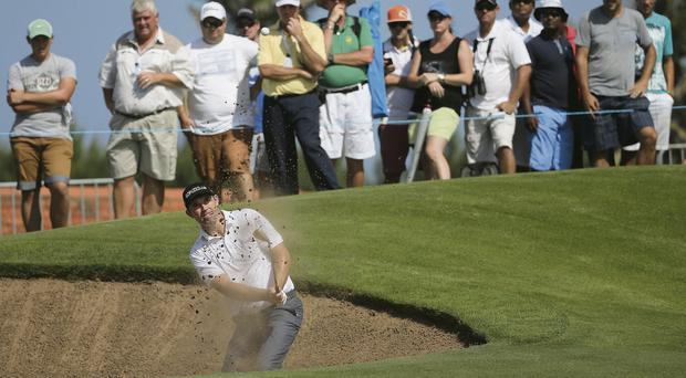 Padraig Harrington escapes from a bunker in South Africa yesterday