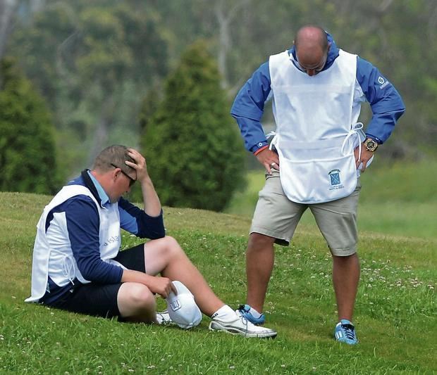 Caddies react after the sudden death of Alastair Forsyth's caddie Ian McGregor during the Madeira Open yesterday. McGregor, 52, from Zimbawe, died after suffering a heart attack on the ninth hole