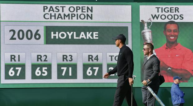 Tiger Woods and Sean Foley walk past a scoreboard at Hoylake showing details of his 2008 Open triumph at the same course