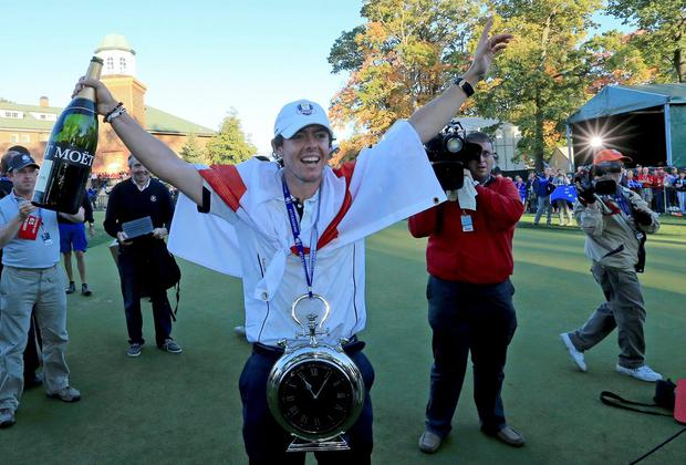 Rory McIlroy celebrates Europe's victory in Medinah after being presented with a clock by team-mates