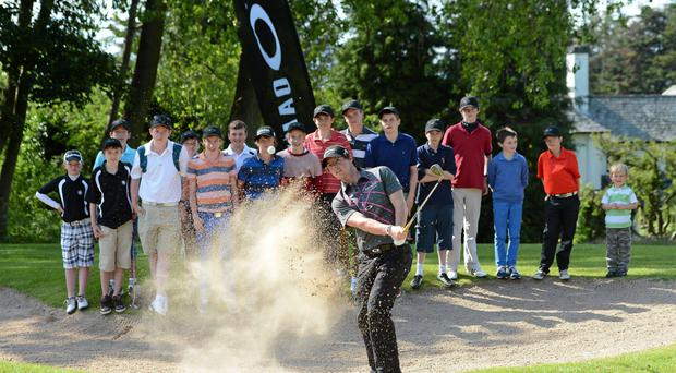 Rory McIlroy demonstrates a bunker shot to a group of junior members at Holywood Golf Club in 2012
