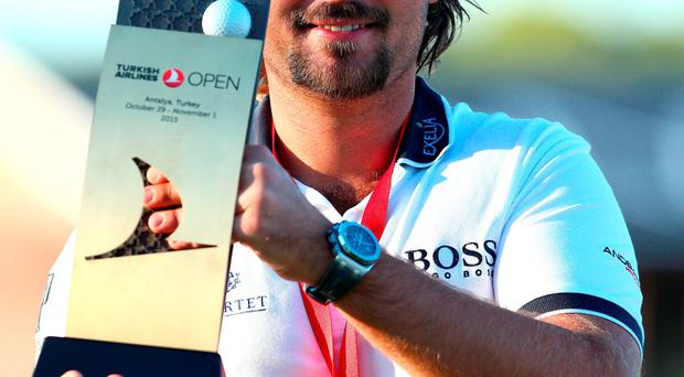 France's Victor Dubuisson celebrates with the trophy after his victory in the Turkish Airlines Open at The Montgomerie Maxx Royal GC
