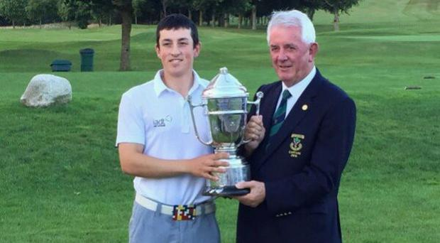 Delgany's Marc Nolan receives the Cup from Carlow's Willie O'Rourke.