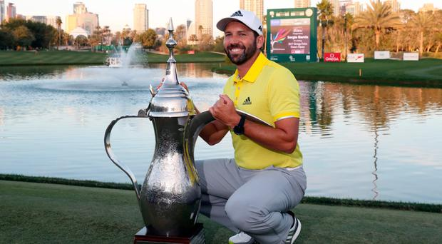 Sergio Garcia celebrates with the trophy yesterday after his victory in the Dubai Desert Classic Photo: AFP/Getty Images