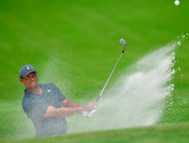 Tiger Woods plays out from a bunker on the fourth hole at Bellerive Country Club yesterday. Photo: Getty