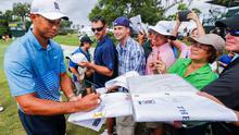 Tiger Woods signs autographs for golf fans while walking off the ninth green during yesterday's practice round at Sawgrass