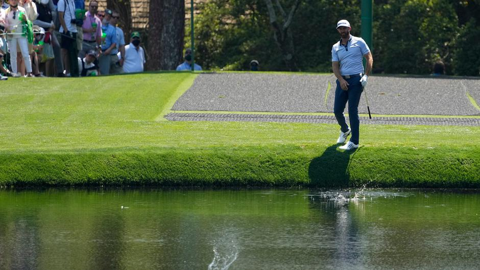 Dustin Johnson skips a ball across the lake onto the green on the 16th hole during a practice round for the Masters. Photo: AP