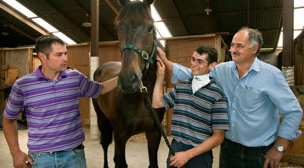 Kevin Smith, owner of Rawnaq with his sons and Matthew, left and Kevin, right, trainer and jockey in his stables in Killmessan, Co. Meath.